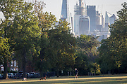 With the skyline of the capital's financial district, the City of London in the distance, man and his dogs walk in Ruskin Park, on 10th August 2018, in London, England.