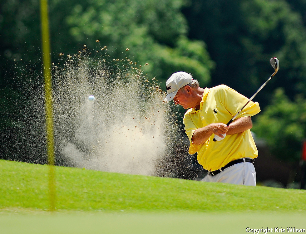 Phil Smith blasts a bunker shot toward the pin at the 18th hole during the Ridgefields Invitational golf tournament on Friday.