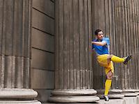 Soccer player kicking ball standing between columns