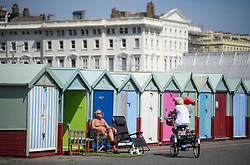 © Licensed to London News Pictures. 03/07/2018. Hove, UK. A elderly man and woman chat to each other next to colourful beach huts on the seafront at Hove, East Sussex on the south coast of England, as a heatwave continues across the UK. Photo credit: Ben Cawthra/LNP