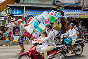 "12 APRIL 2012 - HO CHI MINH CITY, VIETNAM:  A porter delivers plastic goods by hand truck in the nighborhood around Binh Tay Market. Binh Tay market is the largest market in Ho Chi Minh City and is the central market of Cholon. Cholon is the Chinese-influenced section of Ho Chi Minh City (former Saigon). It is the largest ""Chinatown"" in Vietnam. Cholon consists of the western half of District 5 as well as several adjoining neighborhoods in District 6. The Vietnamese name Cholon literally means ""big"" (lon) ""market"" (cho). Incorporated in 1879 as a city 11 km from central Saigon. By the 1930s, it had expanded to the city limit of Saigon. On April 27, 1931, French colonial authorities merged the two cities to form Saigon-Cholon. In 1956, ""Cholon"" was dropped from the name and the city became known as Saigon. During the Vietnam War (called the American War by the Vietnamese), soldiers and deserters from the United States Army maintained a thriving black market in Cholon, trading in various American and especially U.S Army-issue items.        PHOTO BY JACK KURTZ"
