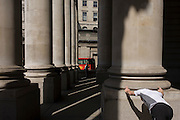 As a jogger stretches, lunchtime spring crowds enjoy warm weather beneath the pillars at Cornhill Exchange in the City of London.