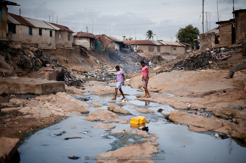Children traverse the polluted gully that divides east and west Nima. Both sides of the community slope down to the river, washing trash and debris into the watercourse. In addition, in the absence of adequate waste collection and sanitation, the river serves as a de facto dumping ground and a latrine.