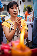 13 APRIL 2013 - BANGKOK, THAILAND:  A woman prays on the plaza in front of Bangkok's City Hall building on the first day of Songkran. Songkran is the traditional Thai New Year's Festival. It is held April 13-16. Many Thais mark the holiday by going to temples and making merit by giving extra alms to monks or offering extra prayers. They also mark Songkran with joyous water fights. Songkran has been a national holiday since 1940, when Thailand moved the first day of the year to January 1.   PHOTO BY JACK KURTZ