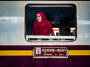 "03 JANUARY 2017 - BANGKOK, THAILAND:         A woman travling on the Bangkok-Yala train opens the window in her train car at Hua Lamphong Train Station in Bangkok Tuesday. Travelers flocked to Bangkok bus and train stations Tuesday, the last day of the long New Year's weekend in Thailand. The New Year holiday in Thailand is called the ""seven deadly days"" because of the number of fatal highway and traffic accidents. As of Monday Jan 2, 367 people died in highway accidents over the New Year holiday in Thailand, a 25.7% increase over the same period in 2016.    PHOTO BY JACK KURTZ"
