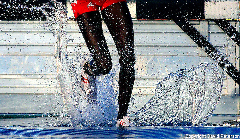A steeplechaser at the 2008 Drake Relays in Des Moines, Iowa, makes a splash as he runs through the water jump barrier.
