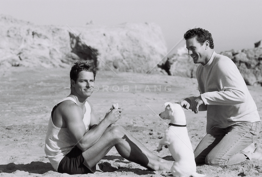 Man and dog begging for food on the beach