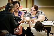 Church member Shirley Clayton (left) and Katy Thomassie, a social work student completing an internship, work with Tamm Leggett and her son Aaron during check-in at the Broadmoor Food Pantry adjacent to Gloria Dei Lutheran Church on Wednesday, March 9, 2016, in New Orleans. LCMS Communications/Erik M. Lunsford