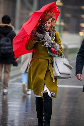 © Licensed to London News Pictures. 14/01/2020. London, UK. Commuters and tourists brave the wind and rain on Westminster Bridge as London braces for more wind and heavy rain during this evening's rush hour. While another storm heads to the South East behind Storm Brendan. Photo credit: Alex Lentati/LNP