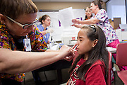 "Oct. 24, 2009 - SCOTTSDALE, AZ: CLY HERNLY-BROWN, RN, gives the H1N1 nasal spray to LESLIE GAMEZ, 9, at Scottsdale Healthcare's Community Health Services clinic Saturday morning. The first publicly administered H1N1 (""swine flu"") vaccinations were given in the Phoenix area Saturday. About 52,000 doses of the vaccine, in both injection and nasal spray form, were available on a first come first served basis, but only to those in so called ""high risk"" groups: pregnant women, children 6 months to 4 years old, children 5 years to 18 years with underlying health concerns and direct caregivers of infants less than 6 months old. More than 700 people lined up at Scottsdale Health Care, which had 500 doses of the vaccine to administer.     Photo by Jack Kurtz"