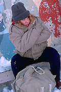 Homeless woman age 43 sitting on bench in the middle of winter.  St Paul Minnesota USA