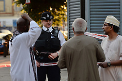 A police officer talks to local people at Finsbury Park in north London, where one man has died, eight people taken to hospital and a person arrested after a van struck pedestrians.