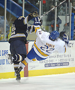 Lake Superior State's Ben Power (right) gets sent flying by Notre Dame's Calle Ridderwall (left) during the Friday night game in Sault Ste. Marie.