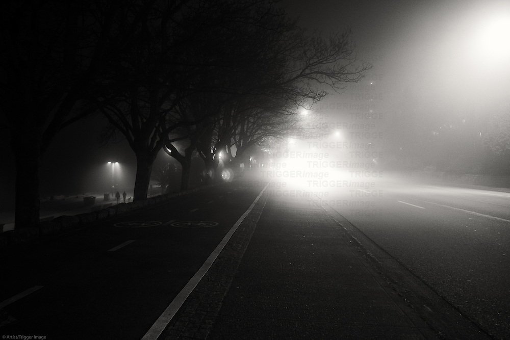 A foggy road with tiny people walking in the distance.