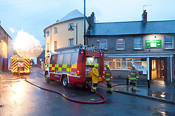 © Licensed to London News Pictures. 13/10/2018. Brecon, Powys, Wales, UK. Fire brigades pump out riverside properties. Storm Callum continues to devastate South Wales. After a night of continuous heavy rainfall, the River Usk breaks it's banks at Brecon in Powys, and floods riverside properties. A local said that it's the worst that she has seen since 1976. Photo credit: Graham M. Lawrence/LNP