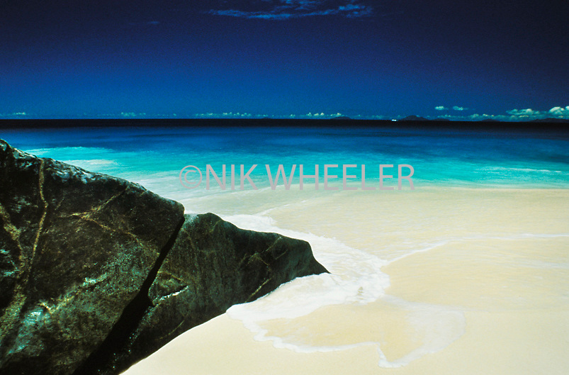 Pristine white sandy beach and turquoise waters of the Indian Ocean at beach in the Seychelles