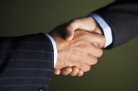 Middle-aged businessmen shaking hands close-up