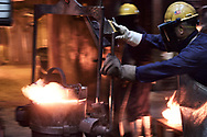 Pacific Steel Casting Company employee moves a bucket of molten alloy  to pour casts