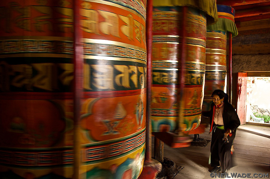 Large Tibetan Prayer Wheels like these might have a mile of prayers inside, bringing the spinner lots of good merit every time they spin one.  This elderly woman has probably spent her whole life spinning wheels just like these.  Dawu (Daofu), Tibet (China).