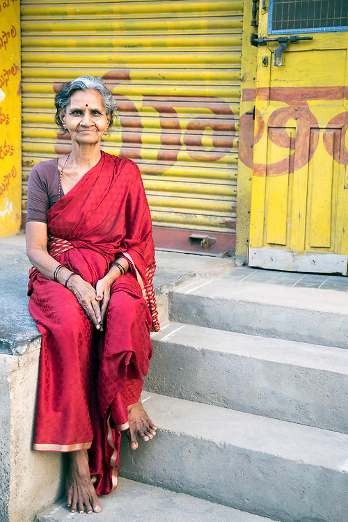 KADIRI, INDIA - 01st November 2019 - Portrait of Indian lady wearing traditional clothing sitting on a step outside closed shops in a retail market in Kadiri, Andhra Pradesh, South India.