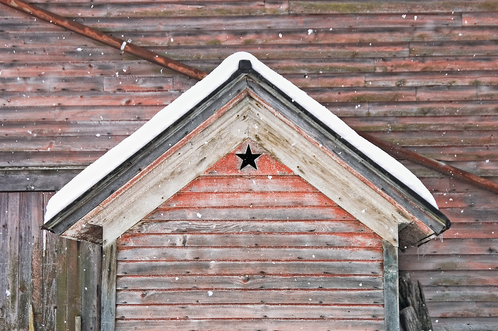 A decorative star cut into the gable of an old weathered carriage house behind a Victorian home while new snow is falling.