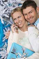 Woman using cell phone with man embracing her by Christmas tree