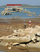 Koh Lanta, Thailand--Two villagers clean up debris  next to the pier which was destroyed by the Tsunami on Koh Lanta island in Thailand.  Two people were on the pier at the time the waves hit.  One was a villager trying to save his boat and the other was a female tourist who was photographing the wave.  Neither one's body has been found.  01/24/05 © Julia Cumes / The Image Works