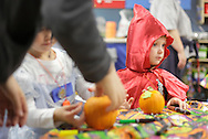 Middletown, New York - Two children wearing costumes decorate pumpkins at the Family Fall Festival at the Middletown YMCA on Oct. 23, 2010.