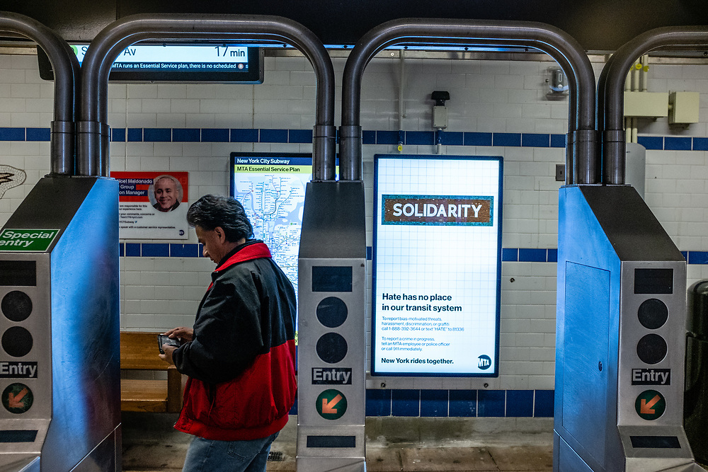 """Brooklyn, NY. 5 April 2020. Signs in the entrance to the Avenue J station on the subway's Q line announce service restrictions, and ask that all non-essential riders stay home. This sign announces """"Hate has no place in our transit system,"""" a result of an increase in hate crimes directed at people of Asian descent."""