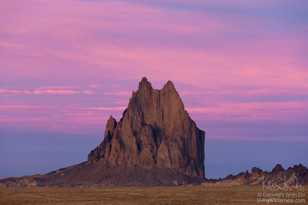"""Pink clouds fill the sky above Shiprock, a prominent peak in northwestern New Mexico. Shiprock is located on Navajo land and is sacred to the tribal people. They call it the """"Rock with Wings,"""" for they believe a bird guided them from the North to settle in the present-day Four Corners area of the United States. Early European settlers thought it looked more like a sailing schooner and named it Shiprock."""