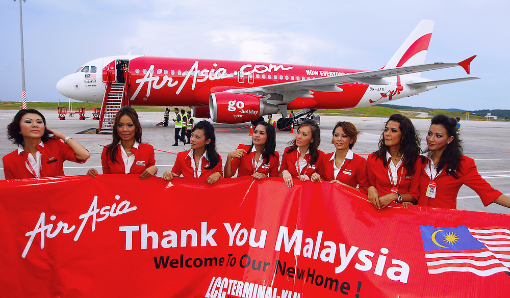 Air Asia stewardress pose infront of their carrier at low cost terminal, Sepang ,Malaysia. Air Asia is Asia's leading low fare, no frills airline based in Malaysia. The airline was established in 1993 and started operations on 18 November 1996. .