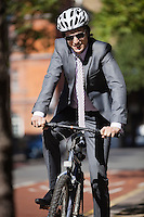 Portrait of happy young businessman riding bicycle