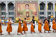 13 APRIL 2013 - BANGKOK, THAILAND:  Thai novices file past the Bangkok City Hall building and a portrait of Bhumibol Adulyadej, the King of Thailand, during a Songkran merit making ceremony at City Hall. Songkran is the traditional Thai New Year's Festival. It is held April 13-16. Many Thais mark the holiday by going to temples and making merit by giving extra alms to monks or offering extra prayers. They also mark Songkran with joyous water fights. Songkran has been a national holiday since 1940, when Thailand moved the first day of the year to January 1.   PHOTO BY JACK KURTZ