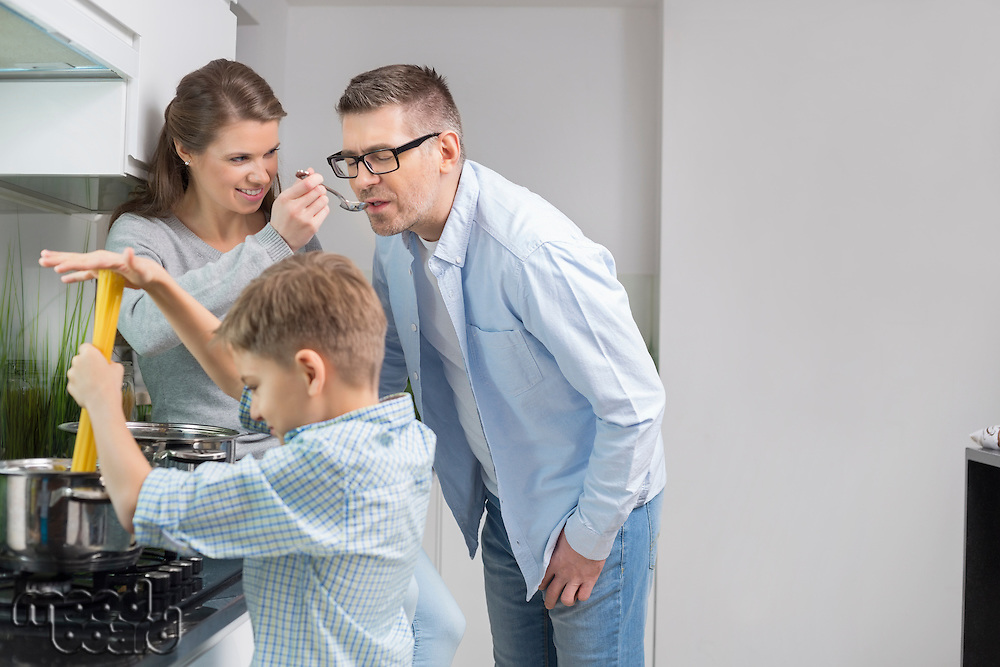 Parents tasting food while son preparing food in kitchen
