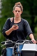 ROTTERDAM een vrouw is aan het appen bellen op de fiets  tijdens het rijden fietsen , telefoon , mobiel , verkeer , gevaarlijk , afleideing , boete , bekeuring , <br /> ROBIN UTRECHT