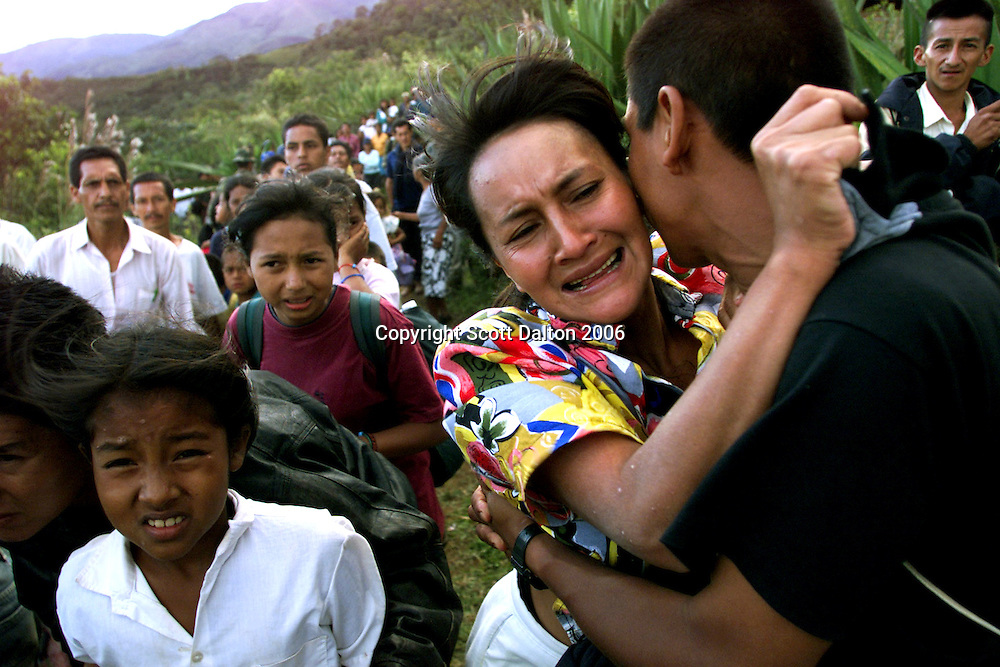 A woman cries as she hugs a loved one before evacuating with fellow villagers on army helicopters from Ortega, a small village about 200 miles southwest of Bogota.  Most residents fled the village after rebels of the Revolutionary Armed Forces of Colombia, or FARC, waged a full-scale attack on the defenseless hamlet leaving behind a trail of mutilated bodies and burned down farmhouses. The FARC were apparently taking revenge the villagers refusal to allow the rebels to recruit local youths into their ranks. Ten villagers were killed in the attack. Colombia has over 2 million refugees who have fled their homes because of attacks by FARC rebels or the right-wing paramilitary. (Photo/Scott Dalton)