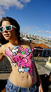 """Meet the naked graffiti girls: Trend for tagging women's bare bodies with street art becomes internet sensation<br /> <br /> Brightly coloured graffiti scribbles and murals are usually found on grotty inner-city buildings.<br /> But thanks to a new internet sensation which sees graffiti-clad girls uploaded revealing shots of themselves, this is one street art trend that has broken out of the mould.<br /> And unlike the illegal vandalism, Graffiti On Girls has become an internet hit, with cheeky street-style art added to women's bodies and the photographs uploaded for all to admire.<br /> Thousands of kinky girls have uploaded pictures of themselves with pieces of work scribbled across their breasts, buttocks and backs. Some have even had graffiti written across their entire body by friends and boyfriends - while one girl has a Bugs Bunny portrait across her breasts. Site owner Vince Prawns said: 'The trend is big. There's now an enormous community of people around the world posting pictures of themselves online.<br /> 'Some of professional models and artist whiles others are the """"girl next door"""" types who just want to give it a try.<br /> 'There are big risks when you do graffiti on the street, but adding your tag to a girl is much nicer - it's all soft and curvy.' The 'graffiti on girls' trend requires either a friend or boyfriend to do the artwork while the female exposes her flesh. Some girls also put tags on themselves, but can't get into hard to reach places such as their back.<br /> Water-based markers like those for outside are used to add the attractive design in a range of colours across the girls' legs or torso.<br /> Vince added: 'The comment that comes up most often on is : """"My two favourites things at one place : Girls & Graffiti"""". 'Graffiti on girls is exclusively for girls, so that means no body art and definitely no guys.<br /> 'There are thousands of pictures online of sexy girls painted by graffiti writers with real style. But we get just as many f"""