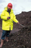 green waste checking the temperate of composted green waste
