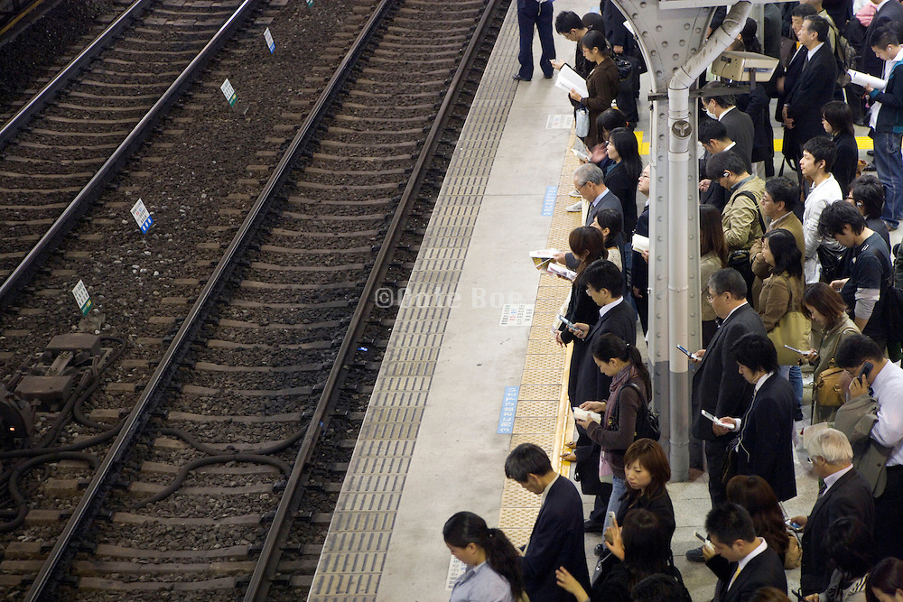 commuters waiting in line for the train to arrive Japan Tokyo