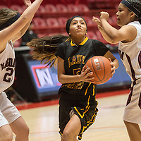 010314      Cayla Nimmo<br /> <br /> Tohatchi Lady Cougar Kalian Mitchell (5) dribbles between two Magdelena players in the tournament championship game held in Albuquerque on Saturday.