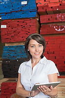 Portrait of an attractive businesswoman using tablet PC with stacked wooden planks in background