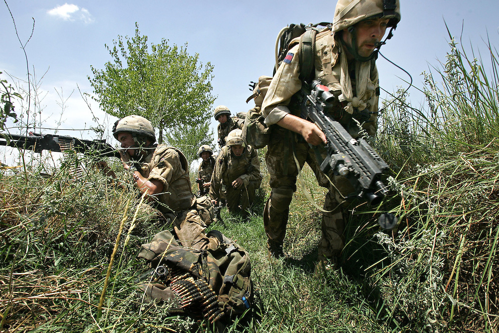 29/06/07..Sangin Valley, Helmand, Afghanistan..Soldiers from A Company 1 Battalion Royal Anglians, known as 'The Vikings' move along a ditch as other members of their unit provide covering fire whilst conducting operations against the Taliban in the Sangin Valley, Helmand province, Afghanistan on the 29th June 2007...The soldiers made a Tactical Advance to Battle over night carrying just food, water and ammunition. At first light they moved on their objectives; a series of compounds, orchards and paddy fields. During the day they exchanged fire with the enemy on a number of occasions. 13 Taliban were killed, 1 British soldier and 3 Afghan troops were wounded.