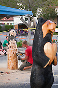 Darin Finnigan sands the base of a black bear sculpture after Ray Schulz demonstrate his chainsaw carving of the Black Bear wooden statues at the Black Bear Diner in Milpitas, Calif. on July 10, 2012.  Schulz has been sculpting bears and other figures with a chainsaw for over 15 years.  Photo by Stan Olszewski/SOSKIphoto.