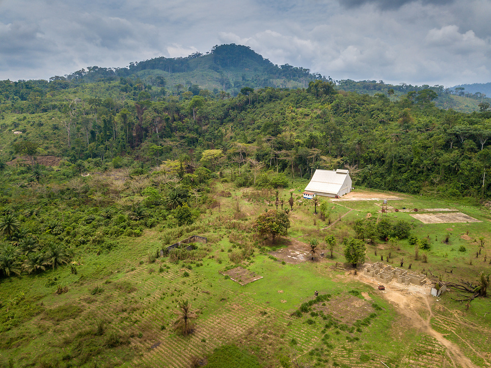 Aerial shot of a farm surrounded by trees and a mountain in Ganta, Liberia