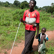 Uganda .  Pamoji village in Pajakoiri Parish, Metu sub-county.  Jamila Bako, who is blind,walking with two of her children in her village.