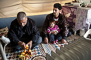 A Syrian family from Idlib province sit in their tent in Islahiye refugee camp, southern Turkey. 02/01/2013