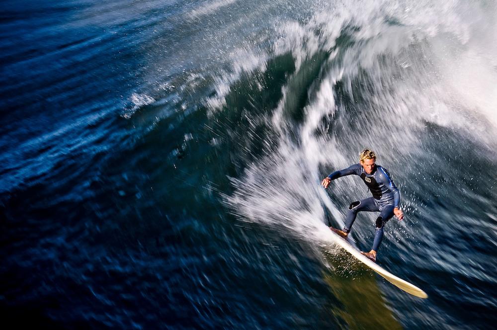 Interfaith blessing of the waves in Huntington Beach, California..Surfer Joey Hawkins of Huntington Beach rides a big wave..Photographer: Chris Maluszynski /MOMENT