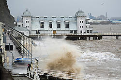 © Licensed to London News Pictures. 05/02/2014. Location, Country. High tide, Penarth: waves crash against the prom with the Victorian pier in the background . Photo credit : Ian Homer/LNP