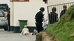 © Licensed to London News Pictures. 13/03/2012. Saltburn, England. Armed police officers watch over  a person (believed to be a woman) lying next to a bag suspected of carrying a bomb (right of woman lying on floor) at Saltburn seafront in Cleveland, North East England on March 13th, 2012. Photo credit : Ian Forsyth/LNP