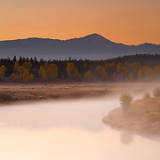 Fog lingers across the waters of Oxbow Bend in Grand Teton National Park, Wyoming.